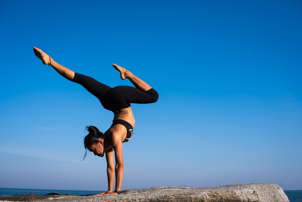 woman black lycra yoga balance blue sky