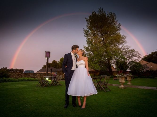 bride and groom in front of rainbow
