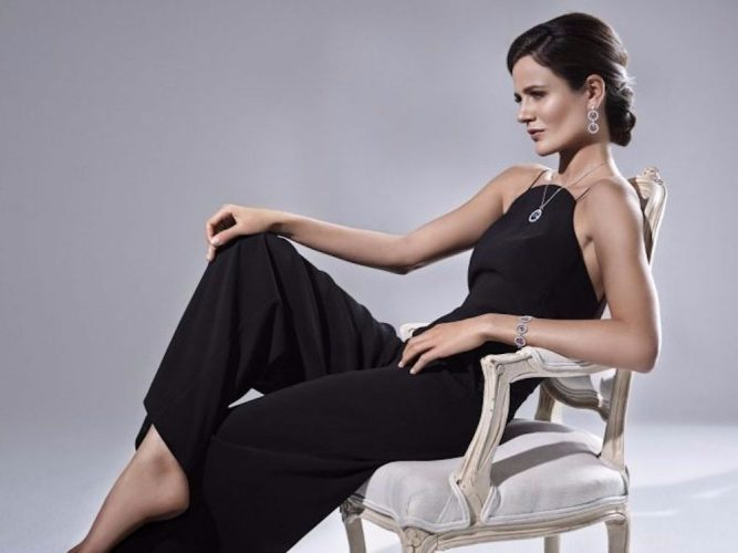 Woman reclining in chair wearing black jumpsuit and Shen London diamonds