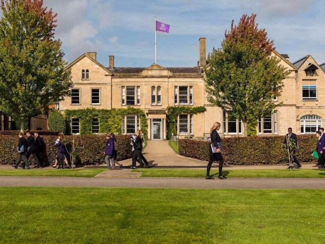 pupils walking in front of Wycliffe Senior School in Stonehouse, sunny day, flag flying, green grass