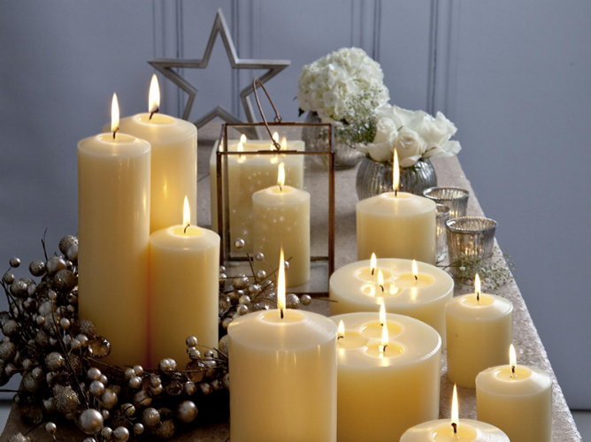 festive cream candles with Christmas decorations including stars, flowers, a lantern and vases