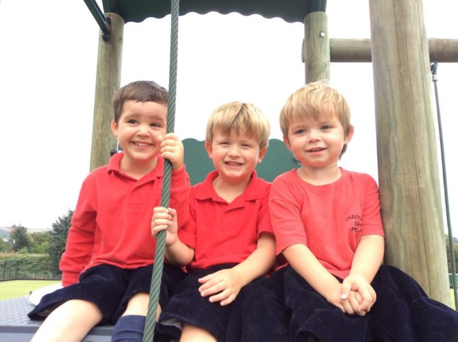 three boys in red tops and blue shorts on a wooden climbing frame at Chafyn Grove