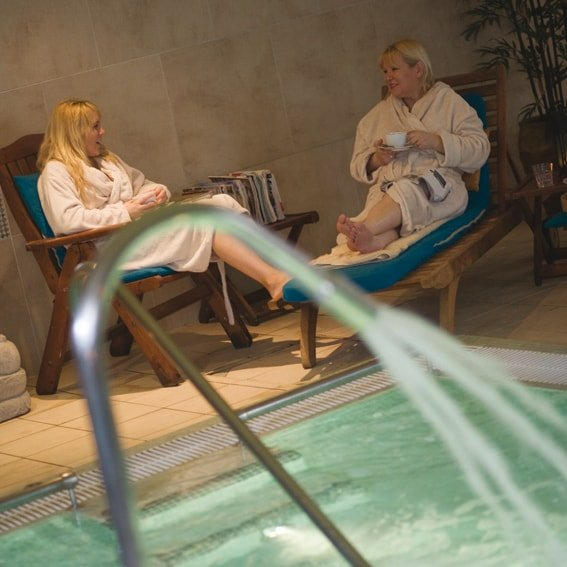 two women in dressing gowns at a spa by the pool