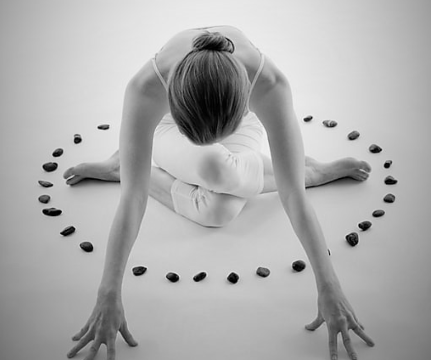 woman doing yin yoga shoelace pose