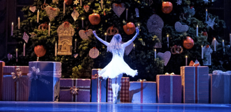 ballerina in The Nutcracker in front of a giant Christmas tree