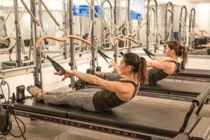 two women doing reformer pilates
