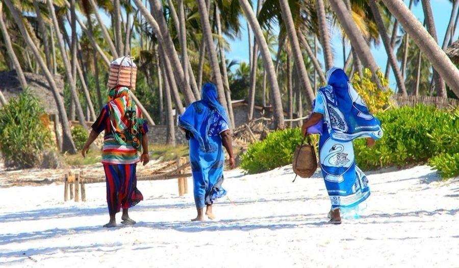 three women walking on a white sandy beach in Zanzibar