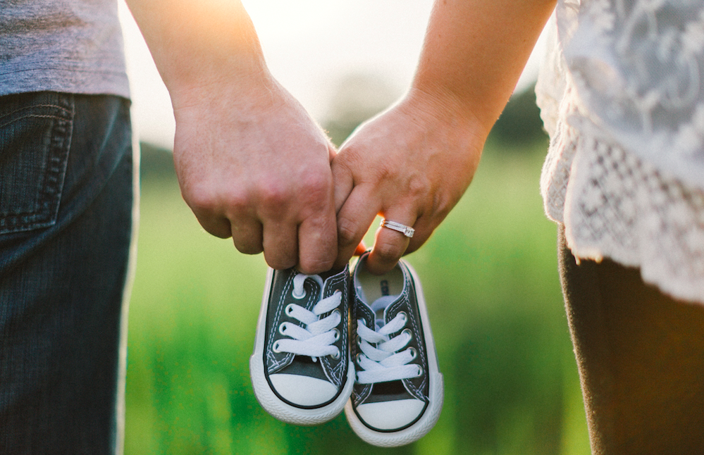 couple holding hands and baby's trainers
