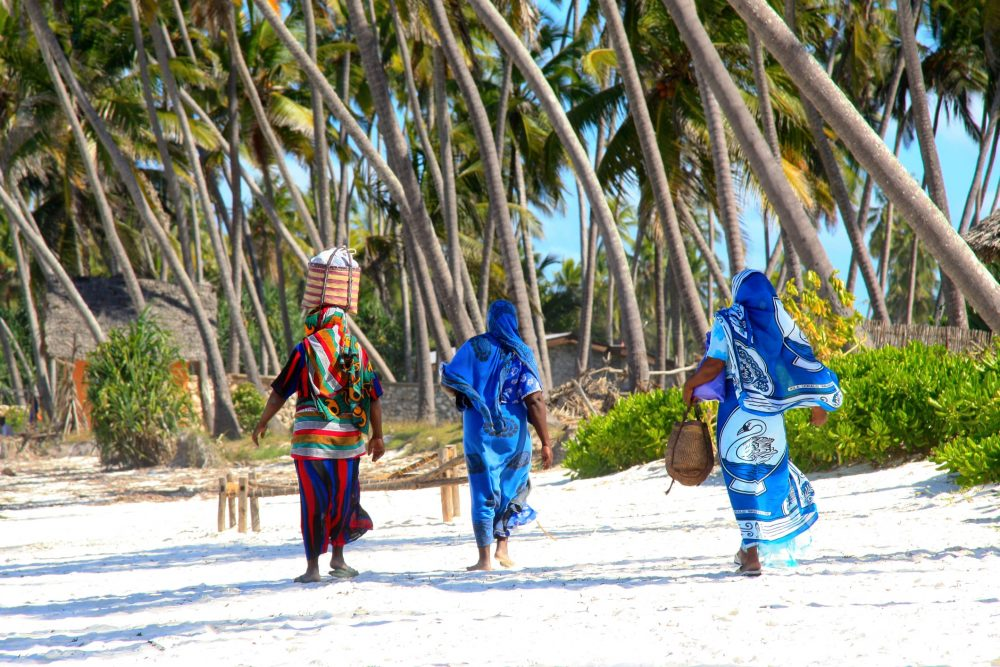 women walking on a beach in Zanzibar