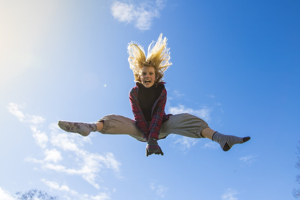 woman jumping in air blue sky