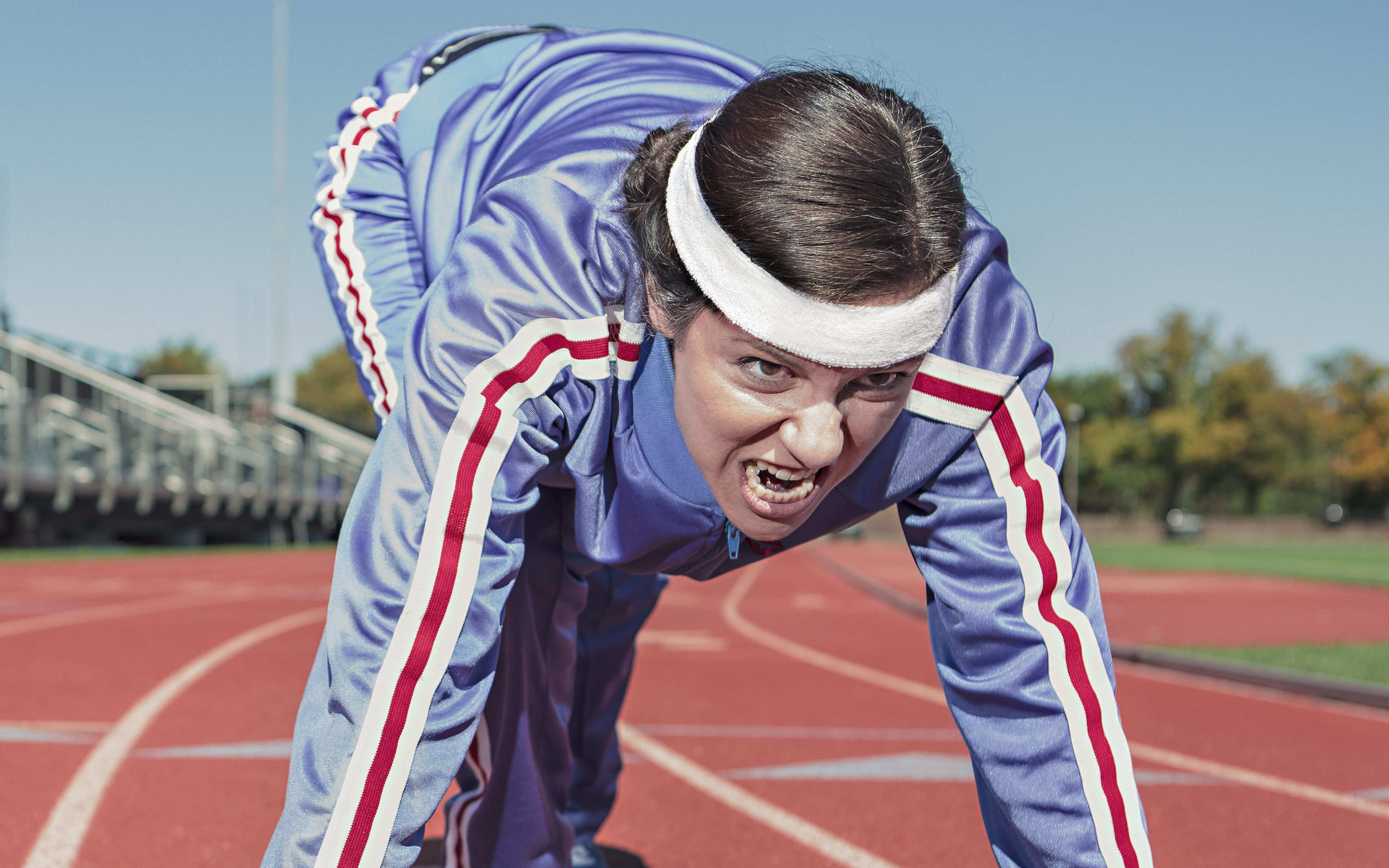 woman in 1970s retro tracksuit on race track about to sprint