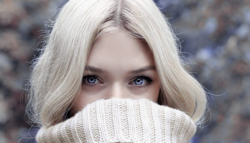 blonde woman in cream roll neck sweater