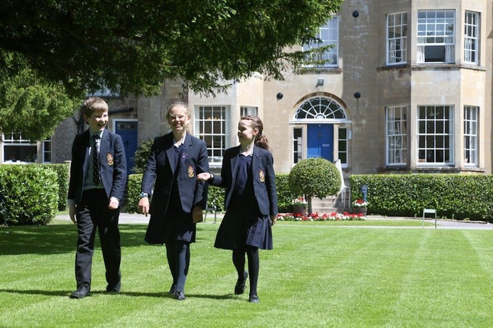 three school pupils in uniform walking on the lawns