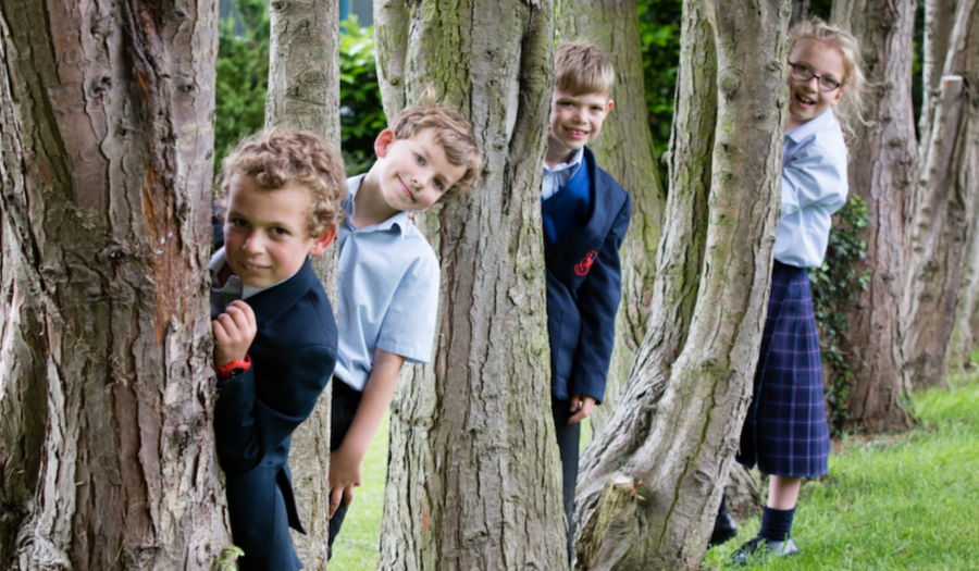 school pupils peaking round trees