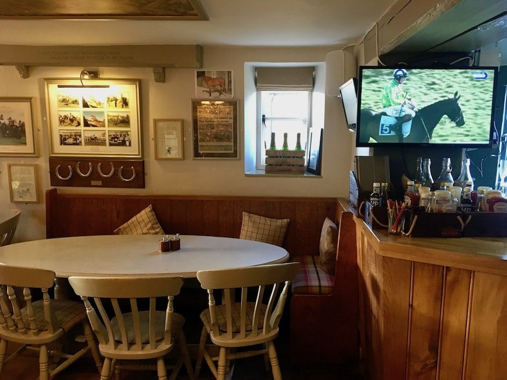 tables chairs TV screen with horseracing on it