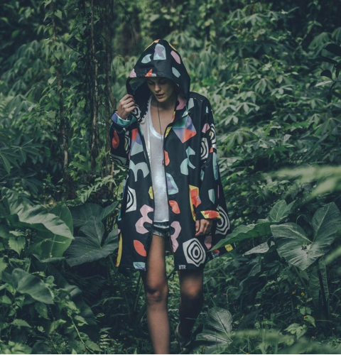 woman in raincoat shorts vest surrounded by greenery in forest hood up