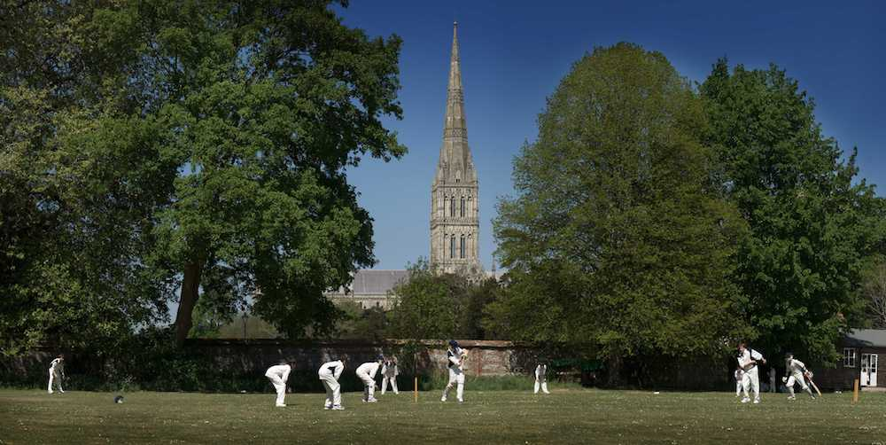 boys playing cricket with Salisbury Cathedral in the background