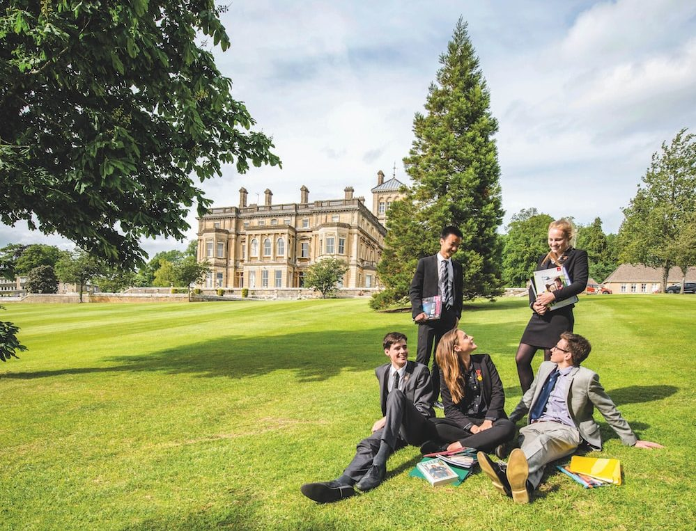 senior pupils sitting on the lawns of Rendcomb