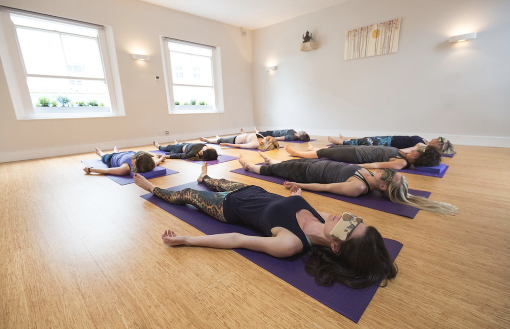 women lying on yoga mats with eye bags
