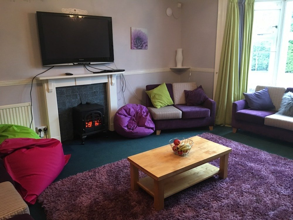 comfy sitting room with pink purple and green beanbags purple rugs flatscreen TV green curtains,