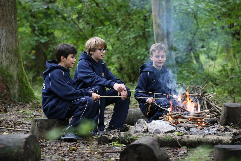 three boys camp fire in the woods