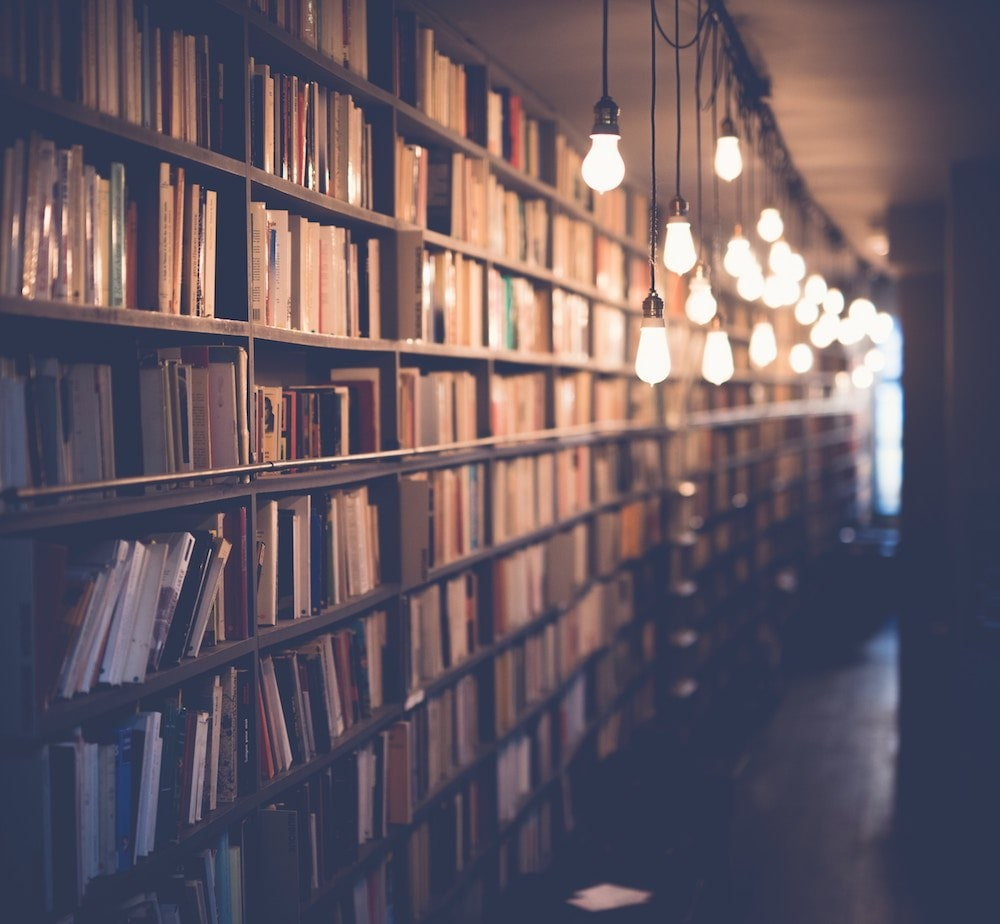 bookcases filled with books, hanging lights