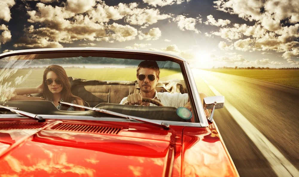 couple in convertible driving at sunset