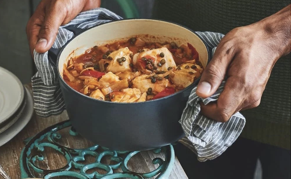 hands holding pot of cod stew in grey Le Creuset pot