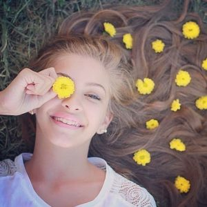 girl lying on grass long brown hair yellow flowers smiling