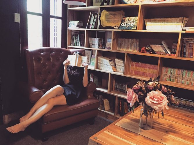 woman in leather chair reading book pink roses in vase bookcase