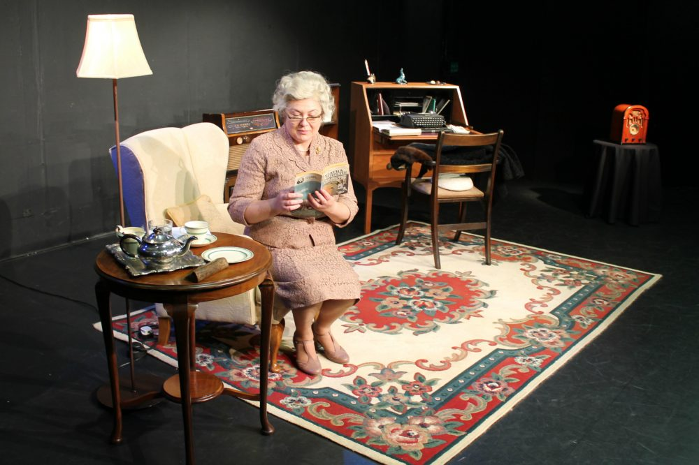 elderly lady in sitting room rug chair desk