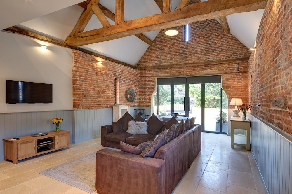 leather sofas, beams brick walls glass doors