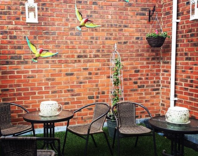 brick wall, tables and chairs roof terrace birds