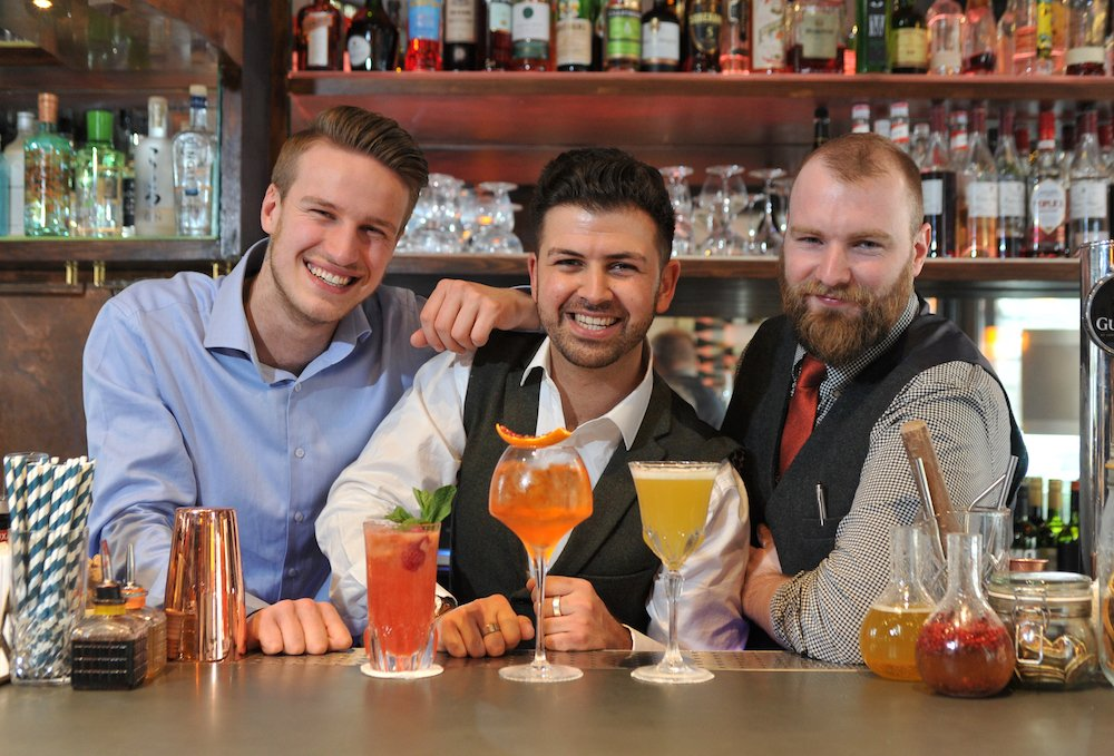 three men at bar cocktails