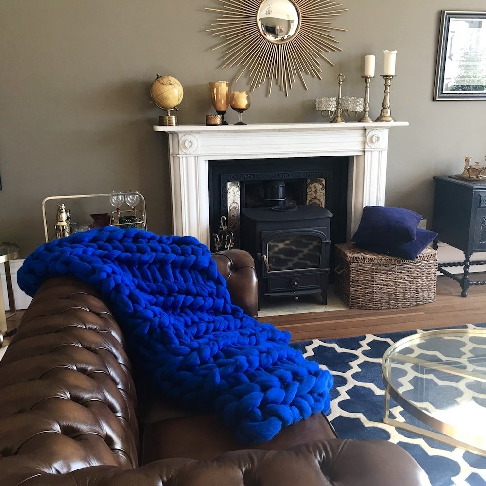sitting room brown leather sofa bright cobalt blue chunky knit throw fireplace