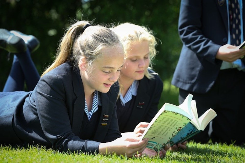 pupils reading exercise book lying on grass