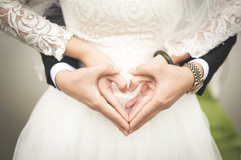 bride and groom holding hands in shape of hearts