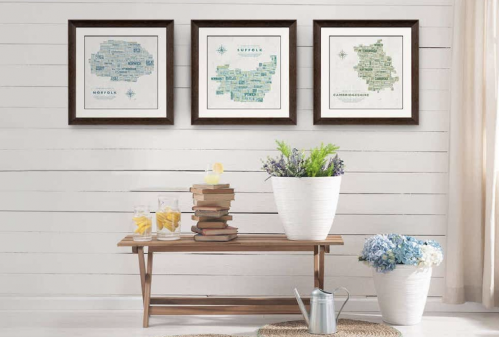 maps, framed, table, plants, white walls, watering can, bench