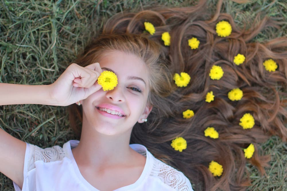 girl lying on the grass hair with yellow flowers