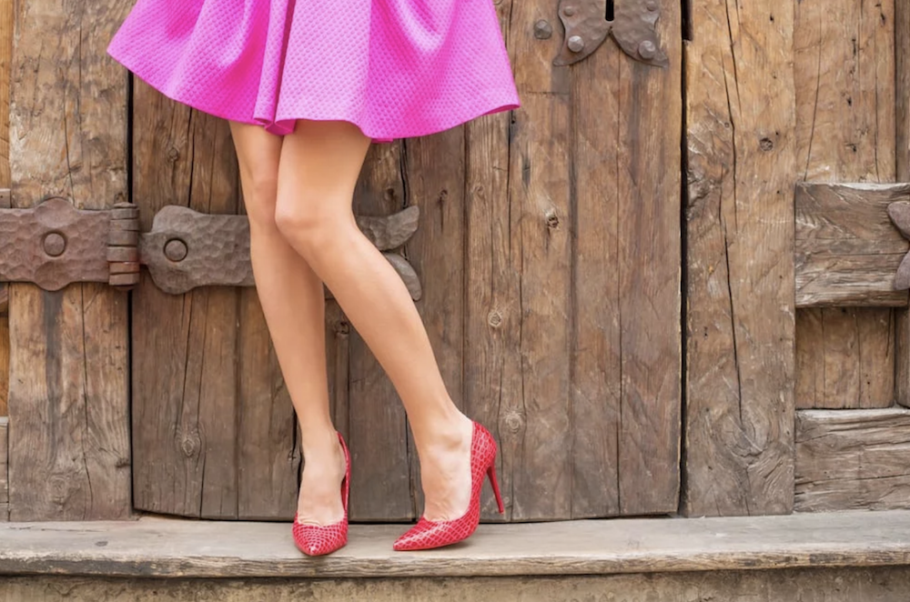 woman wearing short pink skirt and red stilettos in front of barn door