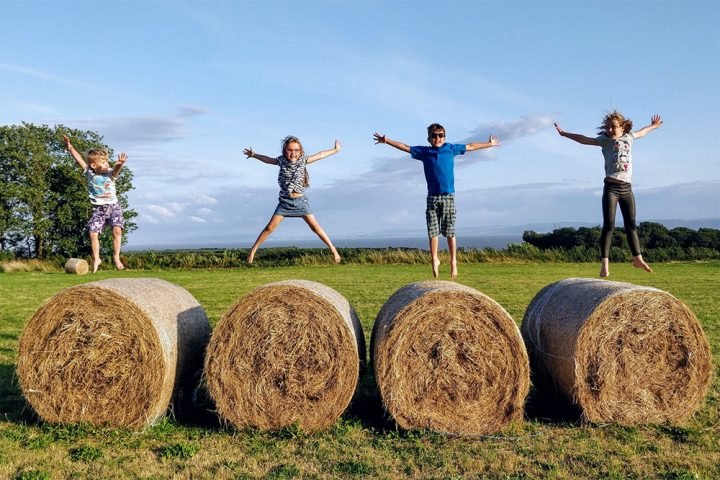 kids jumping on hay